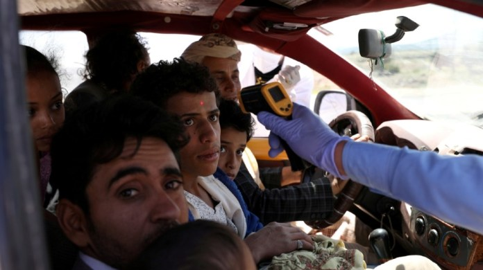 A health worker takes the temperature of people riding a taxi van, amid concerns of the spread of the coronavirus disease (COVID-19), at the main entrance of Sanaa, Yemen May 9, 2020.
