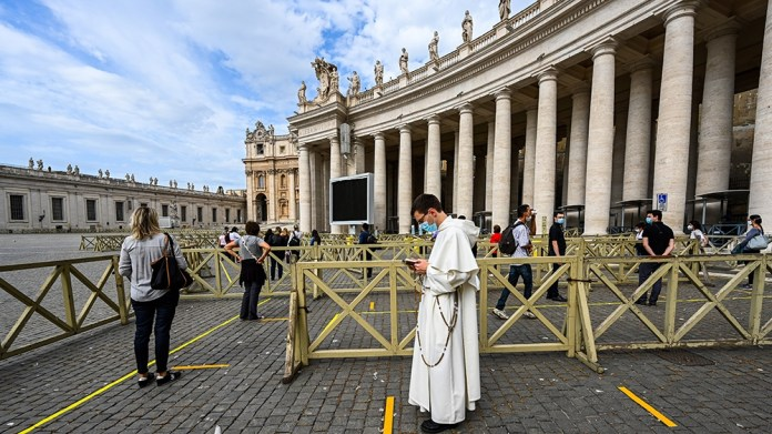 People line up in respect of security distancing to access St. Peter's Basilica on May 18, 2020 in The Vatican during the lockdown aimed at curbing the spread of the COVID-19 infection, caused by the