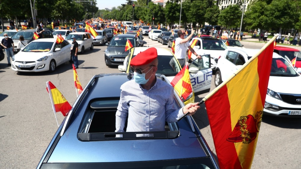 A demonstrator wearing a protective face mask carries a flag during a drive-in protest organised by Spain's far-right party Vox against the government's handling of the