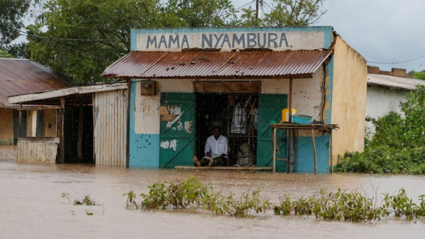 A trader sits at his shop as he looks at the food waters, after River Nzoia burst its banks and due to the backflow from Lake Victoria, in Buyuku village of Budalangi, in Busia County