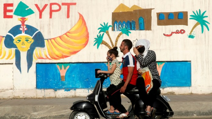 A man rides a motorcycle with his family in Cairo