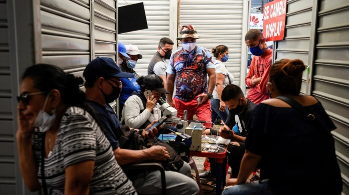 A cell phone repair shop attends customers in a shopping mall as the city allowed some businesses to reopen on Wednesday following a fall in daily deaths due to the outbreak of the coronavirus disease