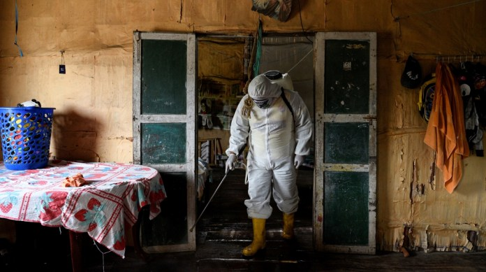 A local volunteer, who is helping to disinfect buildings in his town during the coronavirus disease (COVID-19) outbreak, wears protective clothing as he disinfects a home with a chlorine solution, in