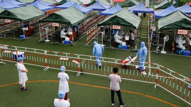 People receive nucleic acid tests, during a government-organised visit to a testing site, following a new outbreak of the coronavirus disease (COVID-19) in Beijing