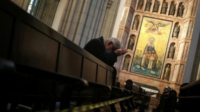 A faithful prays next to blocked sits to keep social distance at Se Cathedral during a mass as the city eases restrictions, amid the coronavirus disease (COVID-19) outbreak,