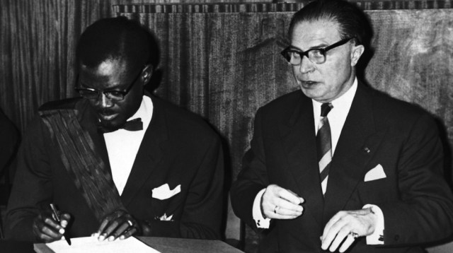 Patrice Lumumba, the Prime Minister of the Congo, signs the act of independence of the Congo in Leopoldville, Congo on June 30, 1960. At right is Gaston Eyskens, Prime Minister of Belgium, who signed