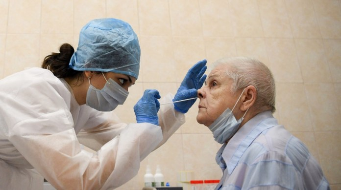 A medical worker wearing protective equipment takes a swab from a woman at a medical facility in Moscow on July 16, 2020, on the first day the Russian capital started providing free testing for the co