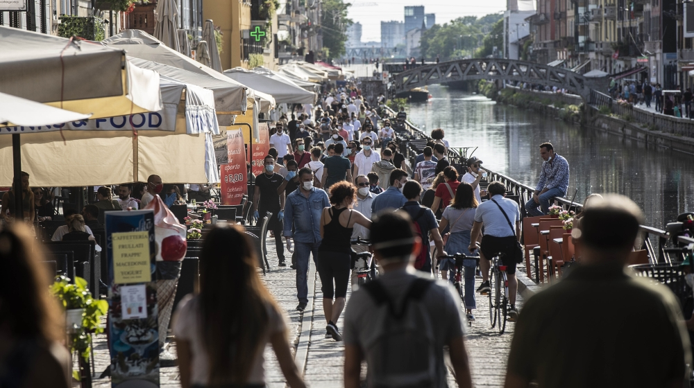 People take a walk and relax at the Naviglio Grande canal, in Milan, Italy, Sunday, May 24, 2020. Europeans and Americans soaked up the sun where they could, taking advantage of the first holiday week