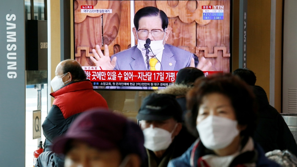 FILE PHOTO: People watch a TV broadcasting a news report on a news conference held by Lee Man-hee, founder of the Shincheonji Church of Jesus the Temple of the Tabernacle of the Testimony, in Seoul