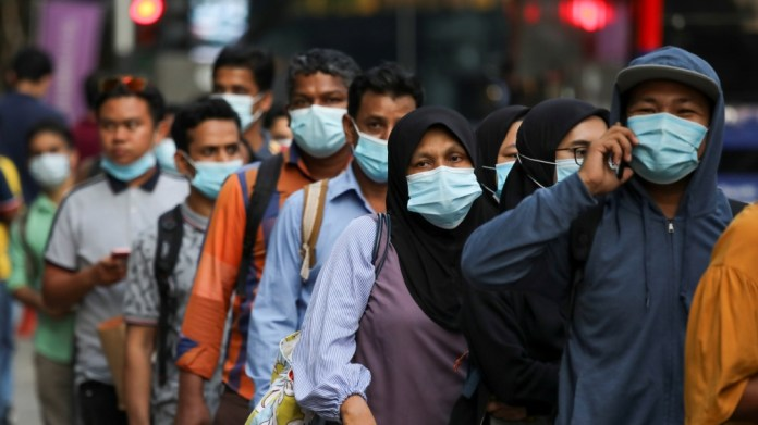 Passengers wearing protective masks wait in line to board a bus at a bus station, amid the coronavirus disease (COVID-19) outbreak in Kuala Lumpur