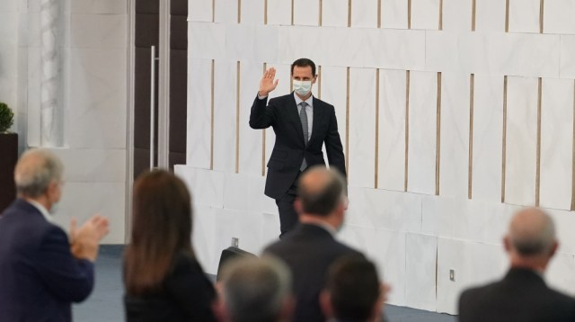 A handout picture released by the official Syrian Arab News Agency (SANA) on August 12, 2020 shows Syrian President Bashar al-Assad greeting members of the People's Assembly in Damascus. SANA / AFP