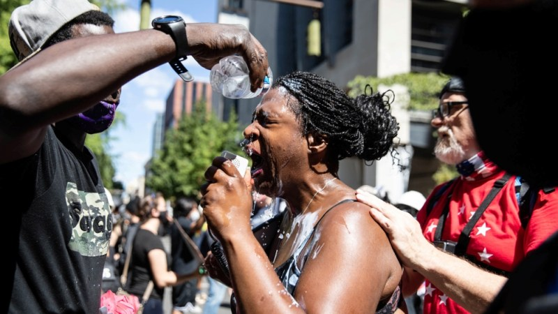 A woman is doused with water as she speaks during a protest against racial injustice in Portland, Oregon, U.S., August 22, 2020. REUTERS/Maranie Staab