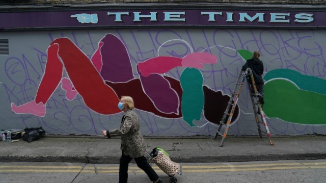 A woman wearing a protective face mask walks past a man painting a mural, amid the coronavirus disease (COVID-19) outbreak, in Dublin, Ireland, August 20, 2020. REUTERS/Clodagh Kilcoyne