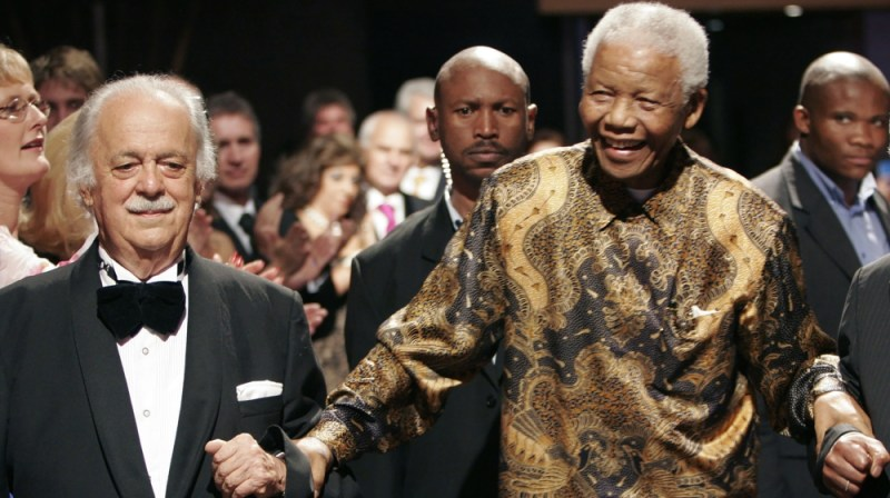 George Bizos, left, anti-apartheid activist, and life-long friend and lawyer of Nelson Mandela, right, arrives for his 80th birthday party in Johannesburg, South Africa. Bizos has died Wednesday Sept.