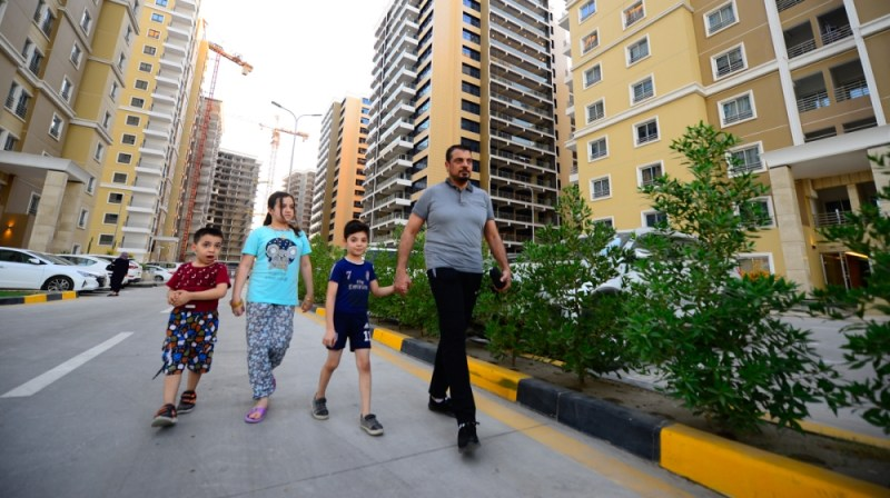 Qabs Kana'an and his children walk through Iraq Gate in central Baghdad. His family moved here in 2019 from Baghdad's Wazirya neighborhood because of better services.  [Haider Hamdani/Al Jazeera]