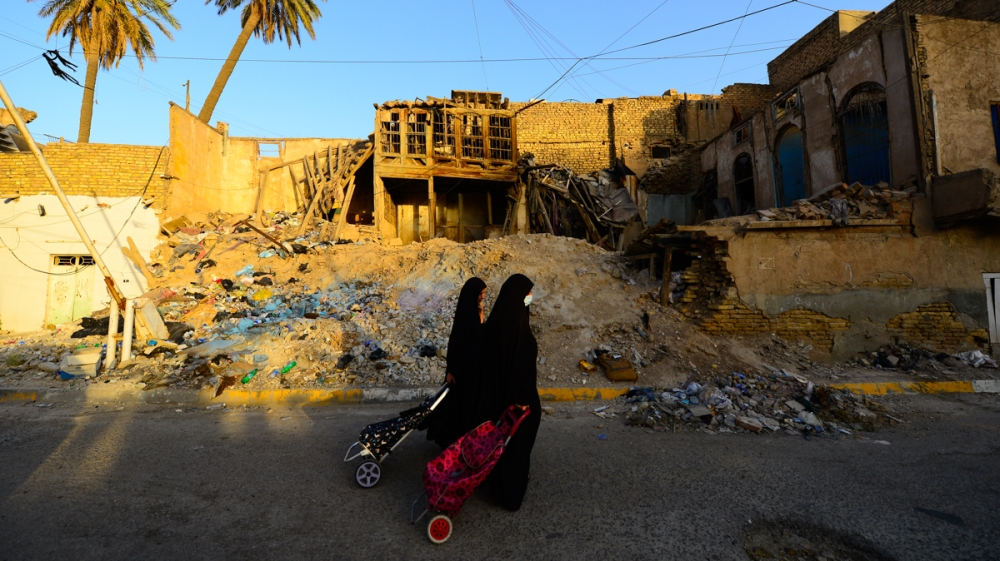 Women walk past a traditional house in Baghdad's Shewake neighborhood. Many of the buildings have collapsed due to neglect, while others have been demolished to make way for new structures. [Haider Ha