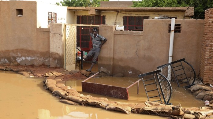 A man stands outside a flooded house in the town of Omdurman, about 18 miles (30 km) northwest of the capital Khartoum, Sudan, Wednesday, Aug. 26, 2020. (AP Photo/Marwan Ali)