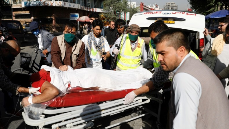 Afghan men carry an injured to a hospital after a blast in Kabul, Afghanistan
