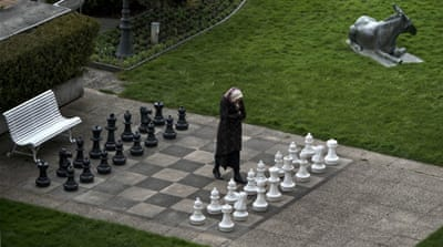 Iranian journalist walks on an open air chess board at the site of nuclear talks in Lausanne, Switzerland [AP]