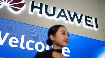 This file picture taken on May 15, 2019 shows a hostess welcoming journalists and guests to the Huawei database and storage product launch during a press conference at the Huawei Beijing Executive Bri