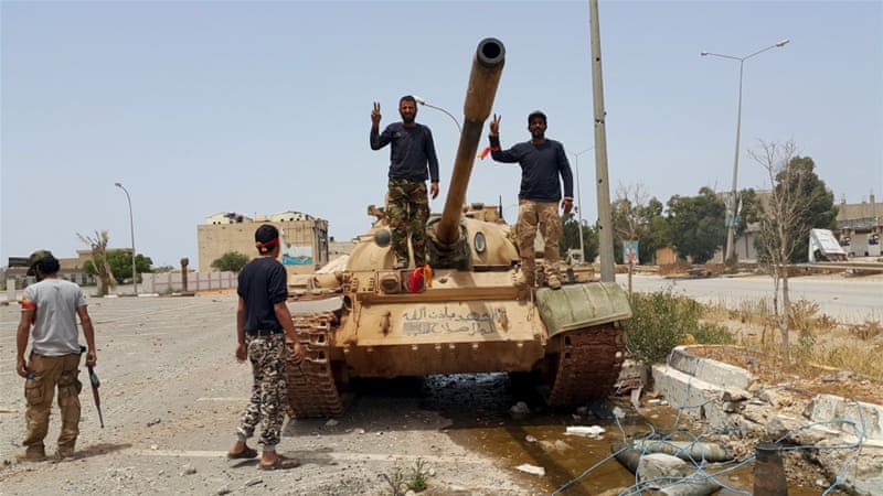 Members of the Libyan pro-government forces gesture as they stand on a tank in Benghazi, Libya, May 21, 2015. [Reuters]