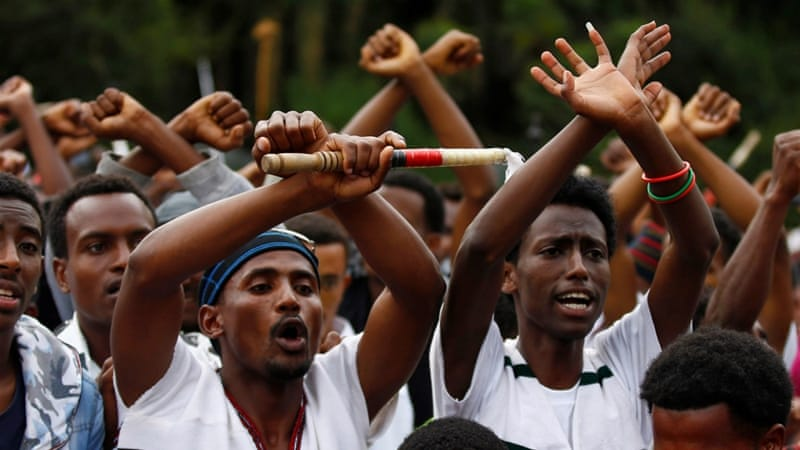 Demonstrators chant slogans while flashing the Oromo protest gesture during Irreecha, the thanksgiving festival of the Oromo people, in Bishoftu town, Oromia region, Ethiopia [Reuters]