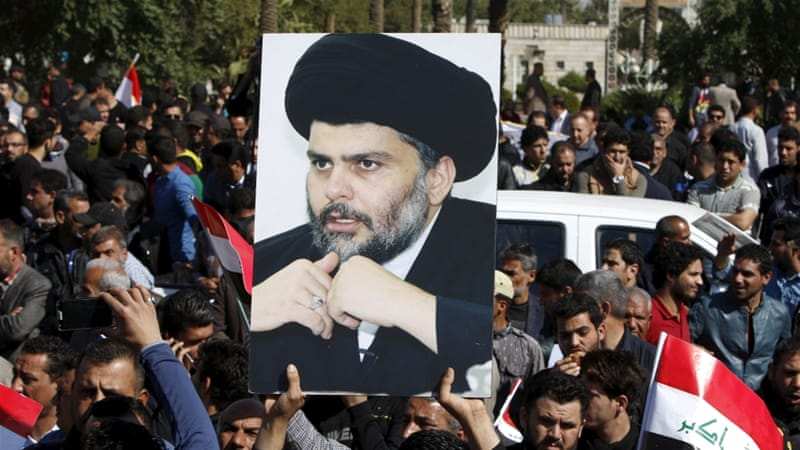 A demonstrator holds a picture of Moqtada al-Sadr during a demonstration in Baghdad [REUTERS]