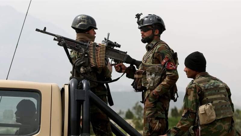 Afghan soldiers stand guard at the entrance of the new parliament after a recent rocket attack [Rahmat Gul/AP]
