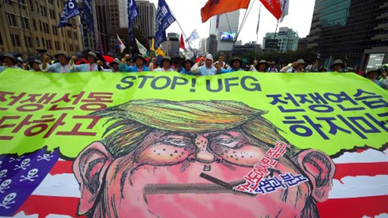 South Korean protesters carry a banner showing a caricature of US President Donald Trump during an anti-US rally demanding peace in the Korean Peninsula in Seoul on August 15 [Jung Yeon-Je/AFP]