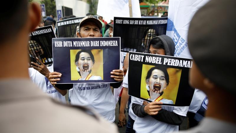 Police officers watch as protesters hold signs against Aung San Suu Kyi, during a rally in support of Myanmar's Rohingya Muslim minority, outside of the Myanmar embassy in Jakarta [Reuters]