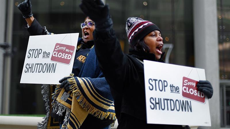 Two government employees in Detroit, Michigan rally against the last government shutdown [File: Paul Sancya/AP Photo]