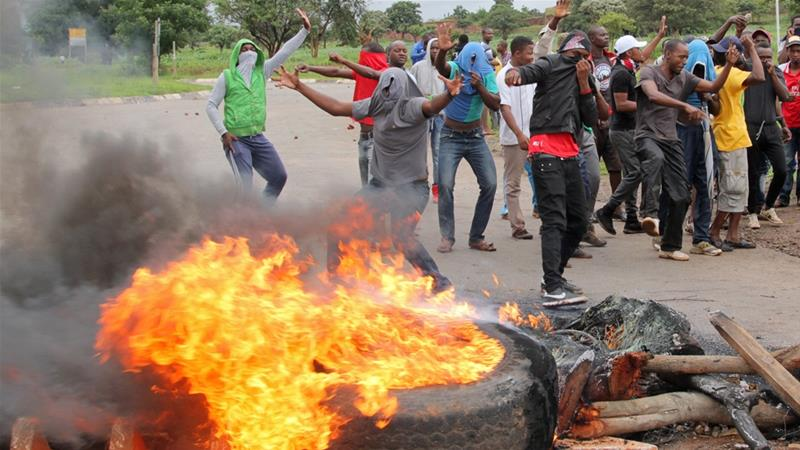 Zimbabweans have taken to burning tyres and police have reportedly responded with deadly force [Philimon Bulawayo/Reuters]
