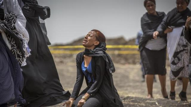 Relatives of crash victims mourn at the scene where the Ethiopian Airlines Boeing 737 Max crashed shortly after takeoff near Bishoftu, south-east of Addis Ababa on March 14 [AP Photo/Mulugeta Ayene]