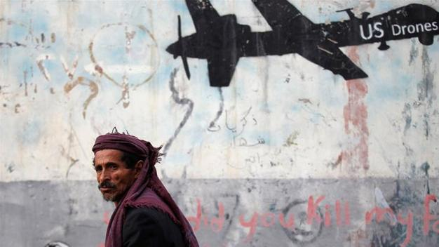 A man walks past graffiti that denounces strikes by US drones in Yemen and that is painted on a wall in Sanaa, Yemen [File: Khaled Abdullah/Reuters]