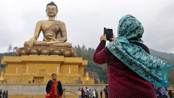 Tourists take photos beside the Buddha Dordenma statue in the town of Thimphu, Bhutan [File: Cathal McNaughton/Reuters]