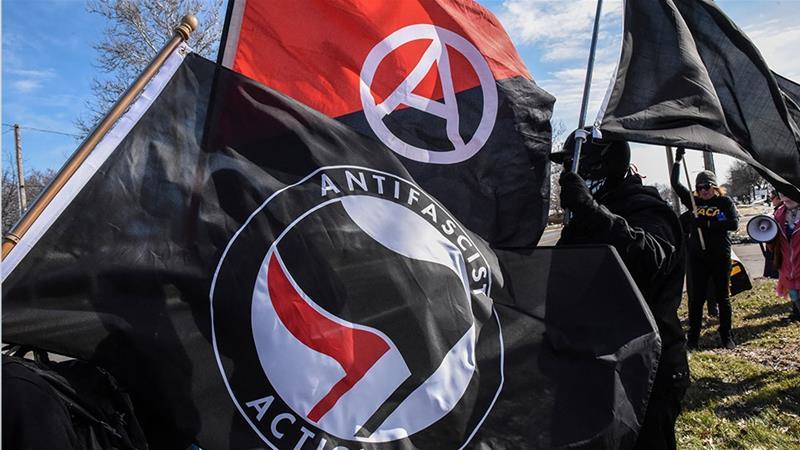 五大湖の反ファシズム組織(Antifa)のメンバーがミシガン州ウォーレンのホテルの外でAlt-rightに抗議して旗を掲げている[File:Stephanie Keith / Reuters]