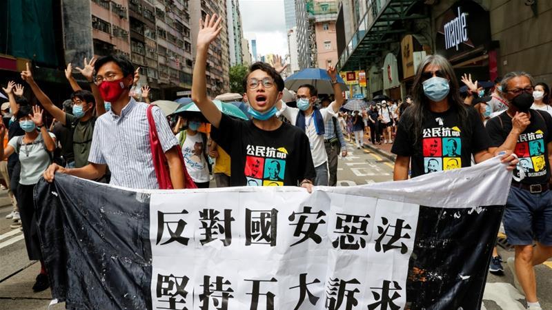 汎民主主義の立法者エディチューホイディック(L)、香港の人権擁護フロントフィゴチャンの副議長、および活動家のレオンクックン(R)は、香港からイギリスへの中国の譲渡の記念日に行進します[ファイル: Tyrone Siu /ロイター]
