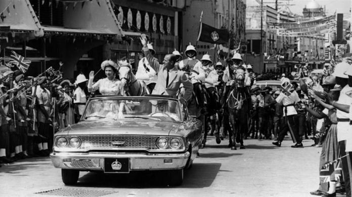 February 18, 1966: Queen Elizabeth and Prince Philip driving through Barbados waving to the crowds [File: Keystone/Getty Images]