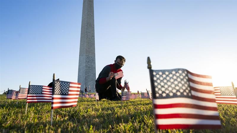 People from the COVID Memorial Project place American flags on the National Mall in Washington DC as the US coronavirus death toll nears 200,000 lives lost [Jim Lo Scalzo/EPA]