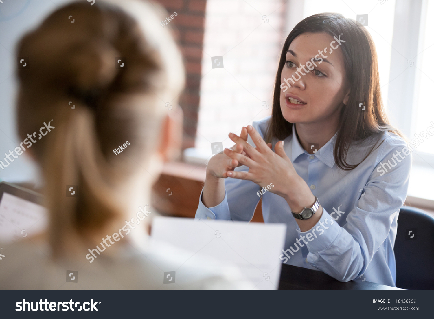 stock-photo-confident-focused-businesswoman-teacher-or-mentor-coach-speaking-to-business-people-at-1184389591