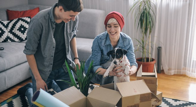 Two people opening boxes in a home
