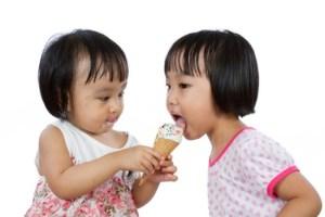 Asian Little Chinese Girls Eating Ice Cream isolated on White Background