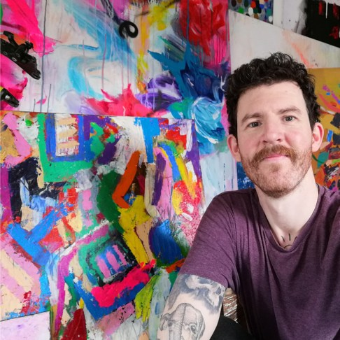 artist allanisart sitting in front of abstract paintings