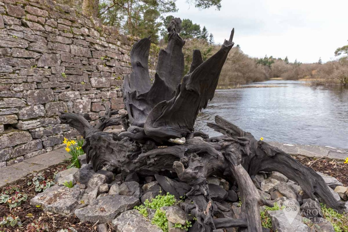 Bogwood sculpture on the riverside in Cong