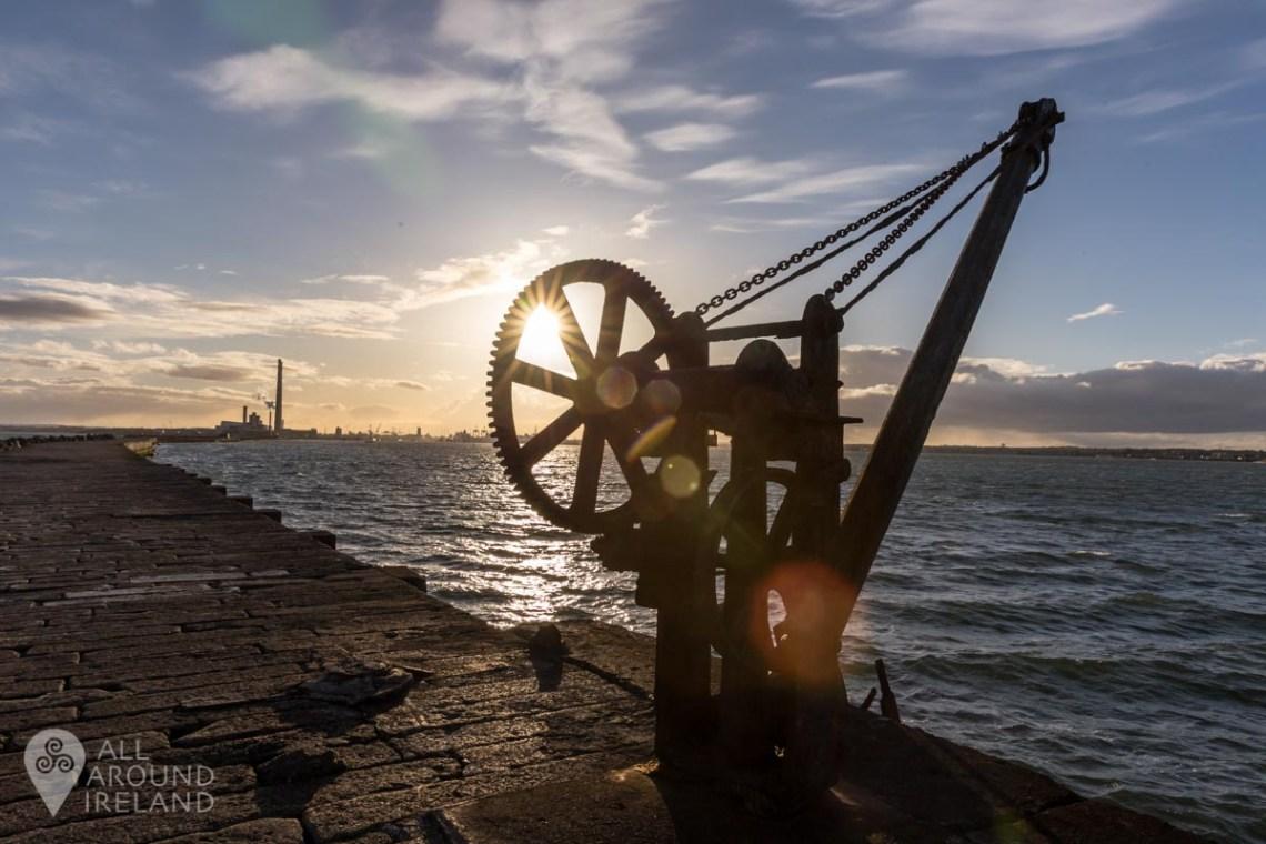 Sun shining through old crane near the lighthouse