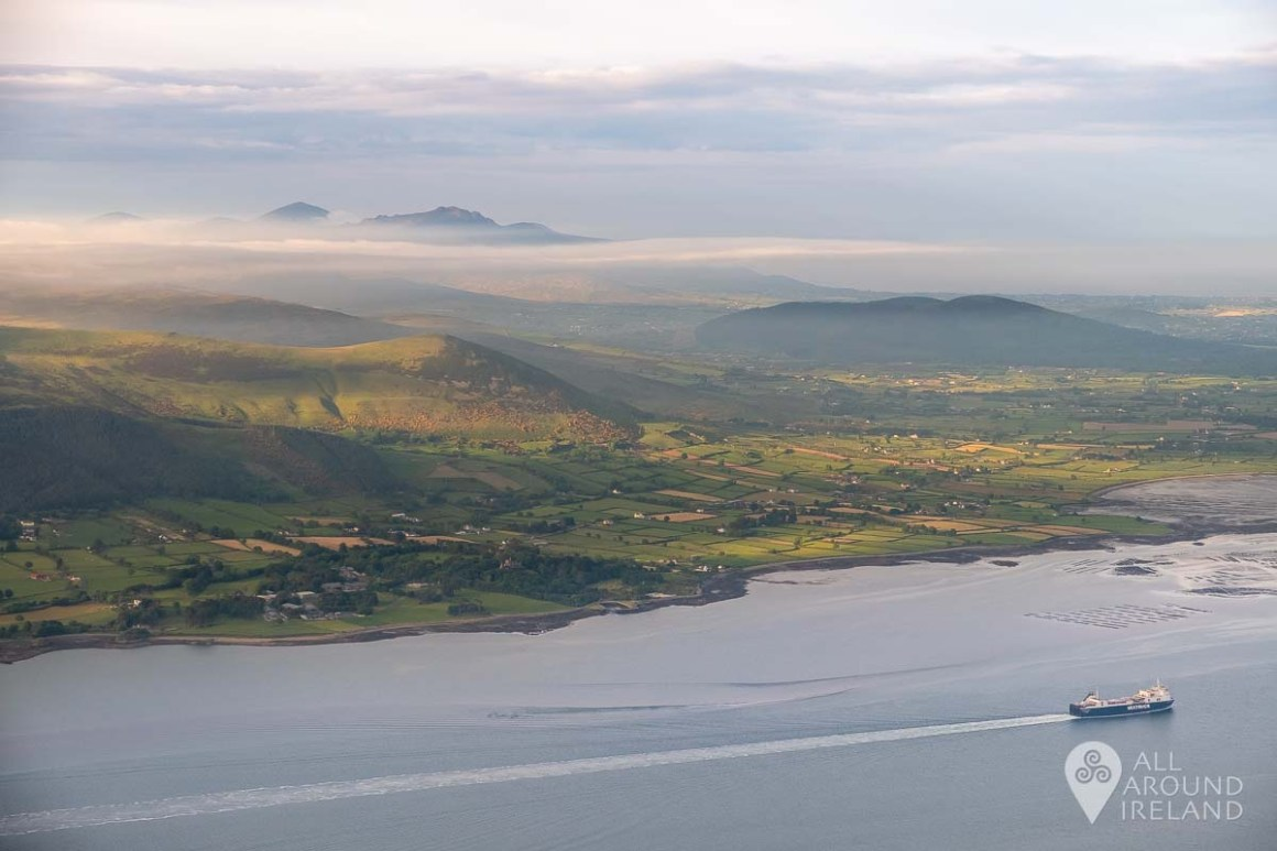 Clouds and golden light over the Mourne Mountains as a ship sails through Carlingford Lough.