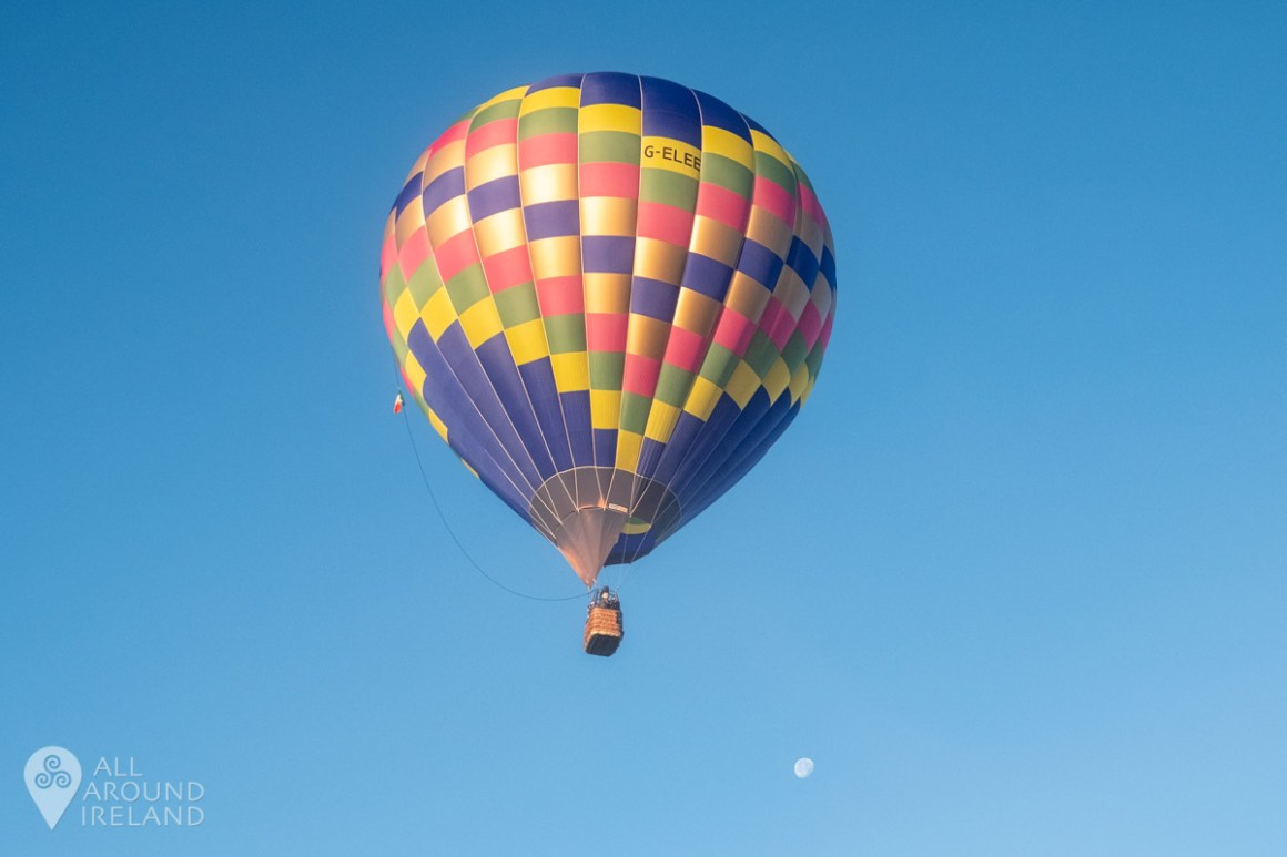 Hot air balloon in flight with moon showing in the sky. Irish Hot Air Ballooning Championships 2018.