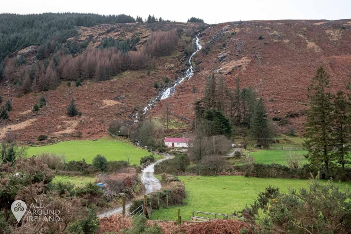 Looking towards Carrawaystick Waterfall from the road. A small white cottage with a red roof sits at the base.
