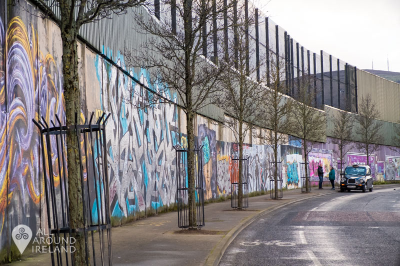 Colourful art stretches along one of the peace walls in Belfast