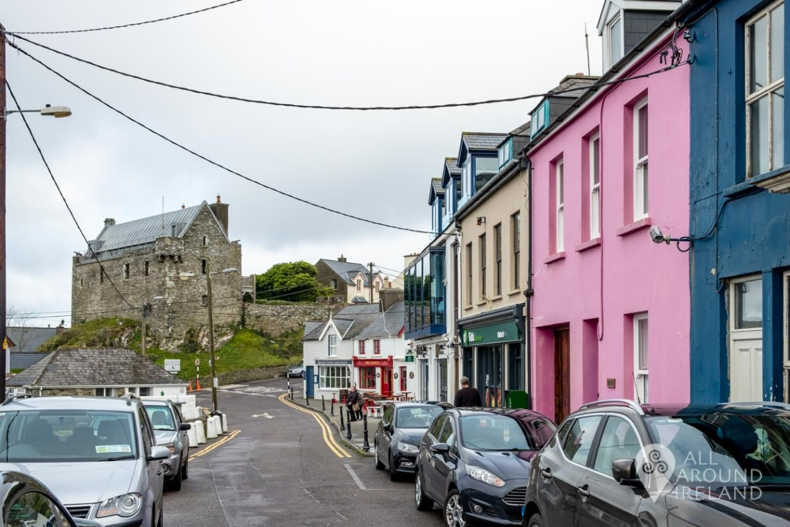 Colourful buildings along the main street in Baltimore village. Dun na Sead Castle is at the top of the road.